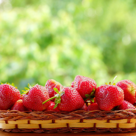 Strawberries in a wicker basket. Blurred background of a summer garden. Greeting card.