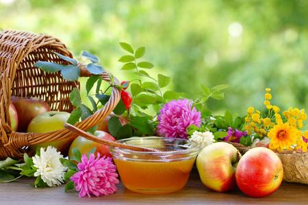 Flower honey, apples and garden flowers. Summer still life. Blurred background.