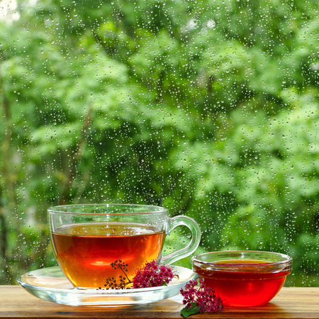 A cup of tea and flower honey by the window. It is raining outside the window. Glass in the drops of rain. Stock fotó - 82057167