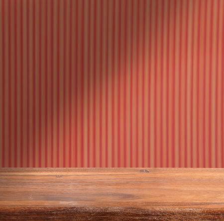 Empty wooden table on the background striped red wall. Blackout.