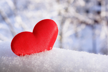 Valentines Day. Red heart in the snow. Congratulatory background.