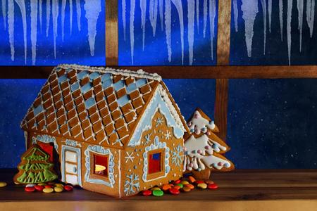 Lebkuchenhaus auf dem Hintergrund des Nachtfensters. Lebkuchenhaus zu Weihnachten. Nachthimmel vor dem Fenster.