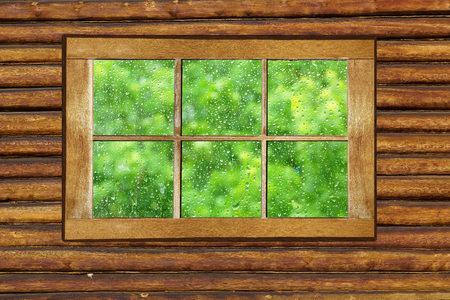 Wooden window with raindrops on the glass. Old shabby window frame on the log wall. Outside the rain.