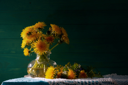 Dandelions in a glass vase. Bouquet of wilting dandelions. Green wooden background. Rustic still life