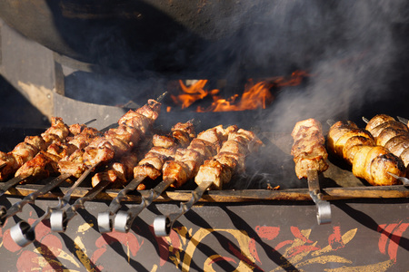 Barbecue. Cooking street food. Meat is fried over an open fire. Festival Moscow Seasons Imagens