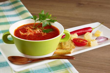 Tomato soup in a green cup on a checkered tablecloth Banque d'images