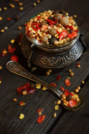 Pepper seasoning in an old bowl. Different varieties of pepper in a shabby cupronickel plate. Black wooden table