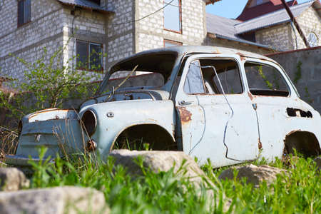 Closeup view of old rusty abandoned white car with peeling paint standing in street outdoors. Horizontal color photography.