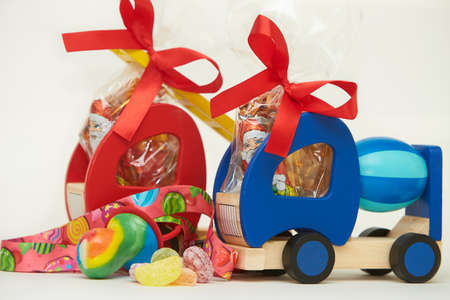 Two toy wooden trucks with gift chocolate and rainbow candies on the white background. Childhood