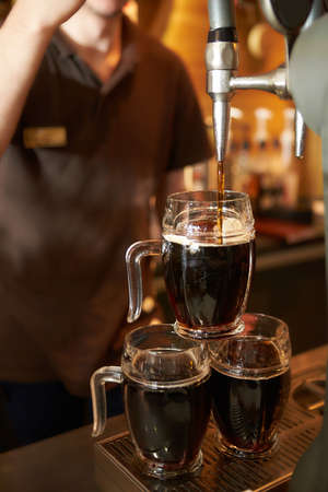 The bartender pours a beer in a beer cups. Draught beer. Imagens