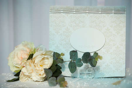 wedding elements, guest book and mini bouquet flowers on table. blue background.