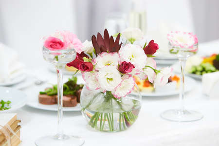 The table of the newlyweds. Interior of restaurant for wedding dinner, ready for guests. Luxury floral arrangement of pink and white flowers in ball glass vases. Wedding decorations, holiday, Catering