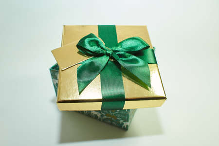 green gift box with gold cover and green ribbon bow with headband for hair, isolated on white background. Christmas picture. bridal flower pearl crystal golden leaves wedding headband for hair Foto de archivo