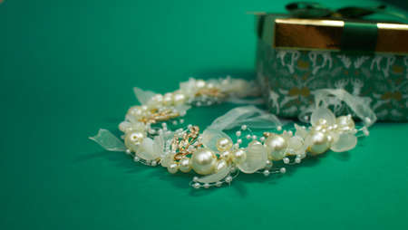 green gift box with gold cover and green ribbon bow with headband for hair, isolated on green background. Christmas picture. bridal flower pearl crystal golden leaves wedding headband for hair