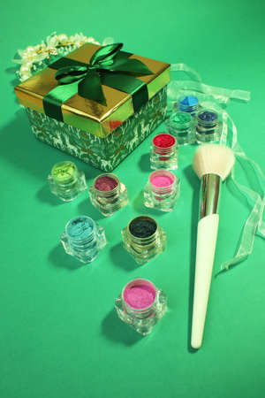 Green gift box with gold cover and green ribbon bow and professional makeup brush and rainbow eye shadow on green background.