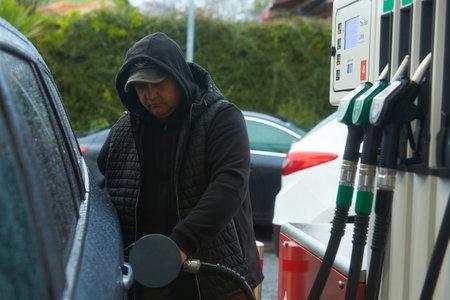 A man refueling a car at a petrol station Stock Photo