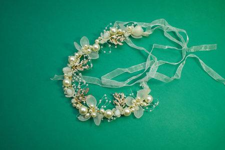 Headband for hair, isolated on green background. Bridal flower pearl crystal golden leaves wedding headband for hair.