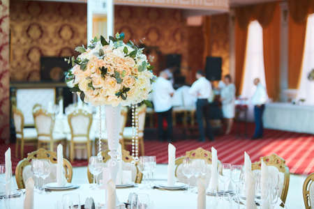 Large pink bouquet of peons, roses and eucalyptus leaves stands on dinner table in luxurious hall. Beautifully decorated in blue green colors wedding hall.