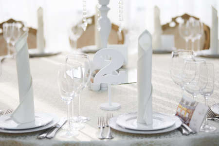Festive table in the banquet hall are decorated with plates, glasses and cards for guests. Standard-Bild