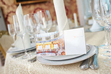 Festive table in the banquet hall are decorated with plates, glasses and cards for guests.