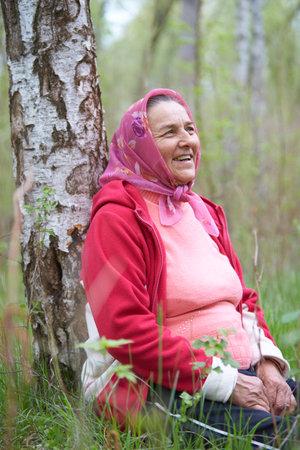 Elderly woman sitting on green grass in spring park.