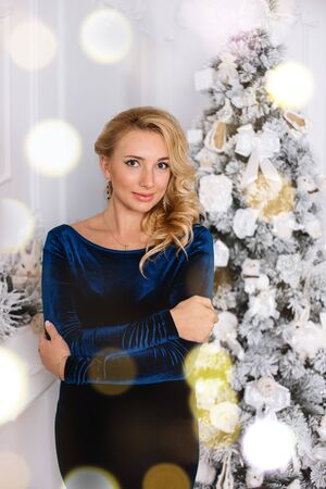 Beautiful blonde looking into your eyes near a Christmas tree