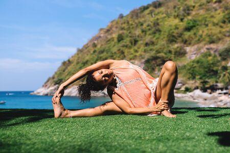 jana shirshasana on a rock early morning near the sea