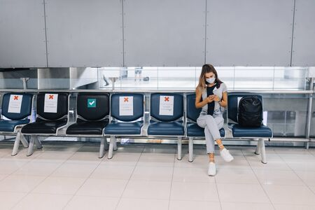 Girl sitting in an empty airport in a mask during a pandemic in Thailand