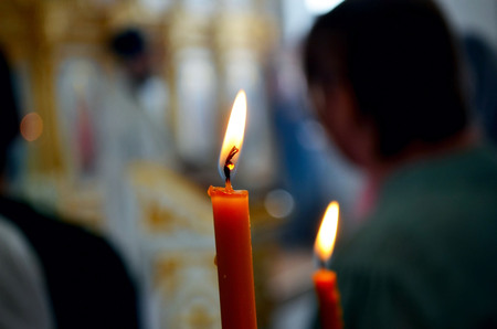 lighted: Picture of a Burning candles in orthodox church.Praying people.