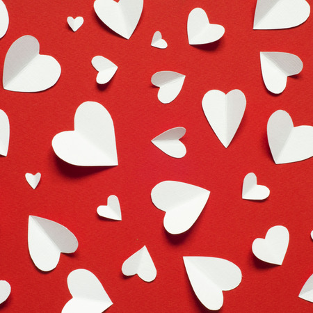 Valentine's day romantic background. White paper hearts at red backdrop, top view. Archivio Fotografico