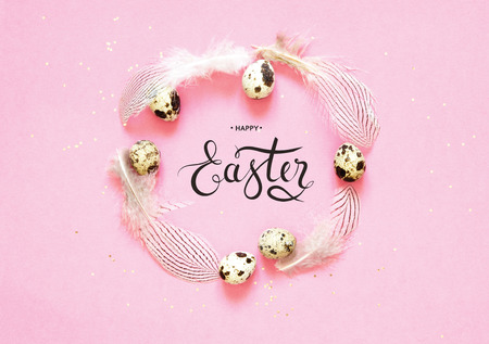 Inscription Happy Easter. Frame with quail eggs, feathering and and golden glitter on pink background. Stock Photo