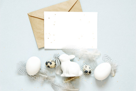 Blank greeting card, kraft envelope. Easter composition with easter eggs, rabbit and feathers. Flat lay, top view.