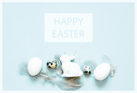 Inscription Happy Easter. Easter composition with easter eggs, rabbit and feathers. Flat lay, top view. Reklamní fotografie