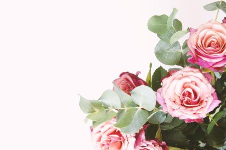 Composizione di fiori. Fiori delle rose ed eucalipto del ramo su fondo bianco. Vista dall'alto, copia dello spazio. - Immagine