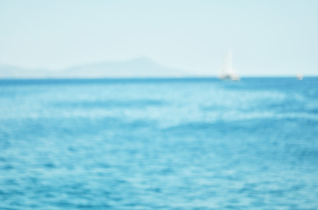 Blurred Sea water surface and waves stretch out to the horizon where islands are visible far away.  - Image