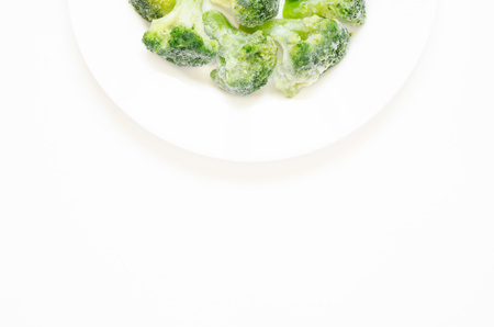Frozen broccoli on a white plate. Top view, flat lay, copy space.