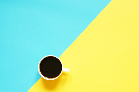 Flat lay cup of black coffee on yellow  and blue background. Minimalistic food concept. Imagens
