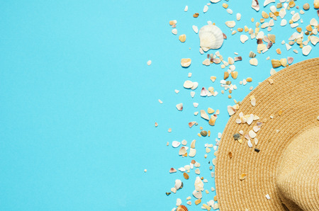Summer vacation concept flat lay. Hat and seashells on blue background. Copy spase. - Image