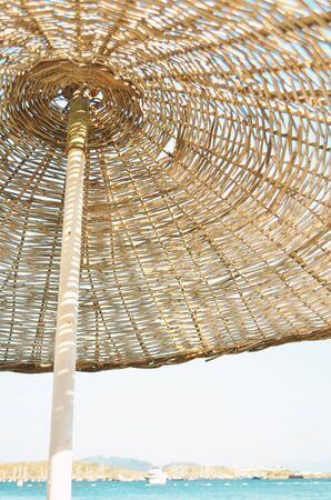 Straw umbrella on the beach and sea background. Summer conсept. - Image