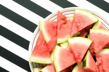 Fresh red watermelon slice in plate on striped background. Summer concept. Top view, Flat lay. - Image
