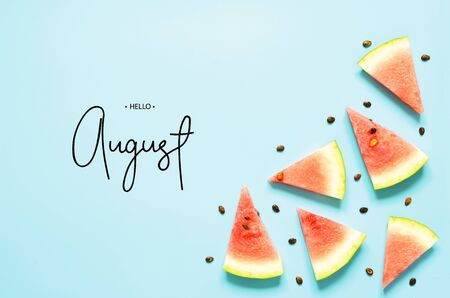 Inscription Hello August. Fresh red watermelon slice Isolated light blue background. Top view, Flat lay. - Image 免版税图像