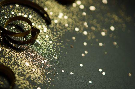 Golden sparkles and ribbons on black background. Festive concept. - Image