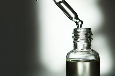 Cosmetic or medical glass bottle with pipette. Skin care concept. Natural hard light, deep shadows. - Image Stock Photo