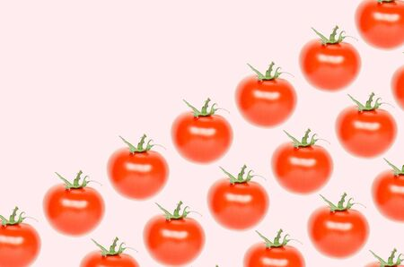 Colorful pattern of red tomatoes on pink background. - Image Stock Photo