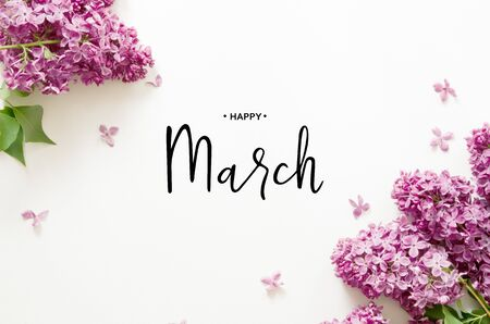 Inscription Happy March. Lilac flowers on white background. Spring flowers. Top view, flat lay. - Image Foto de archivo