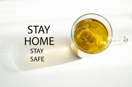Stay at home and be safe. Self isolation and quarantine campaign to protect yourself and save lives. Herbal tea, shadow and sun rays.