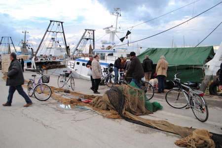 Rimini, Italy, November 19, 2010: People on a fisherman's area. Nets on the ground