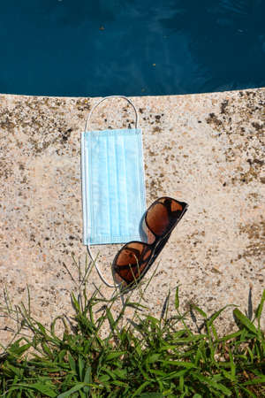 Blue face mask for protection against the Corona Virus (COVID-19), sunglasses laying beside a swimming pool during coronavirus worldwide pandemic holidays