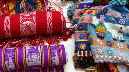 Handicraft souvenirs from Peru - woolen knitted hats and alpaca scarves with tradition design at the international fair on Independence day of Cuenca Stock Photo