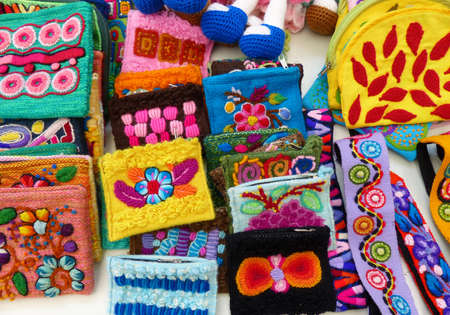 Handcraft souvenirs from Peru - colorful embroidered purses and other textile with traditional peruvian design at the Indian market in Lima